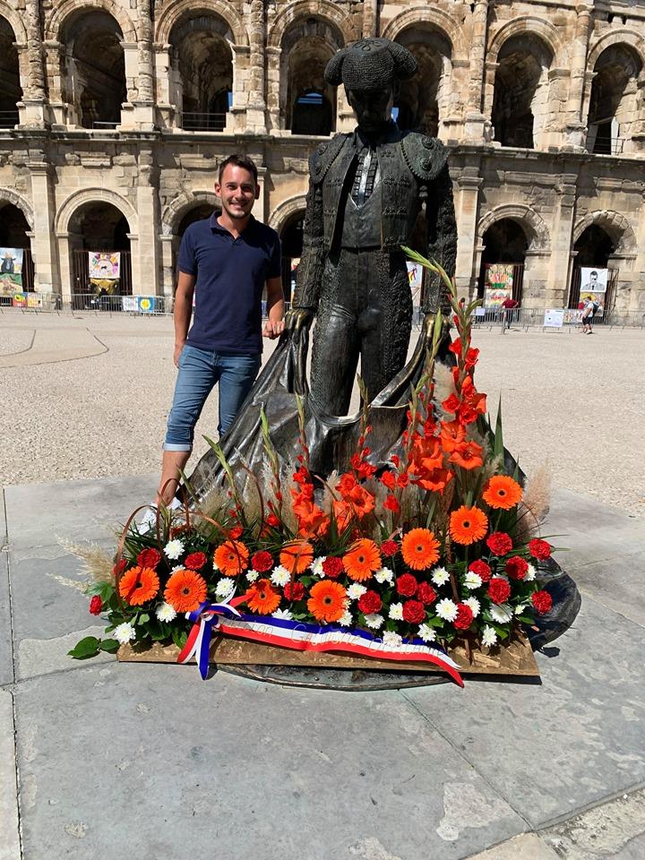 Statue fleurie devant des arènes