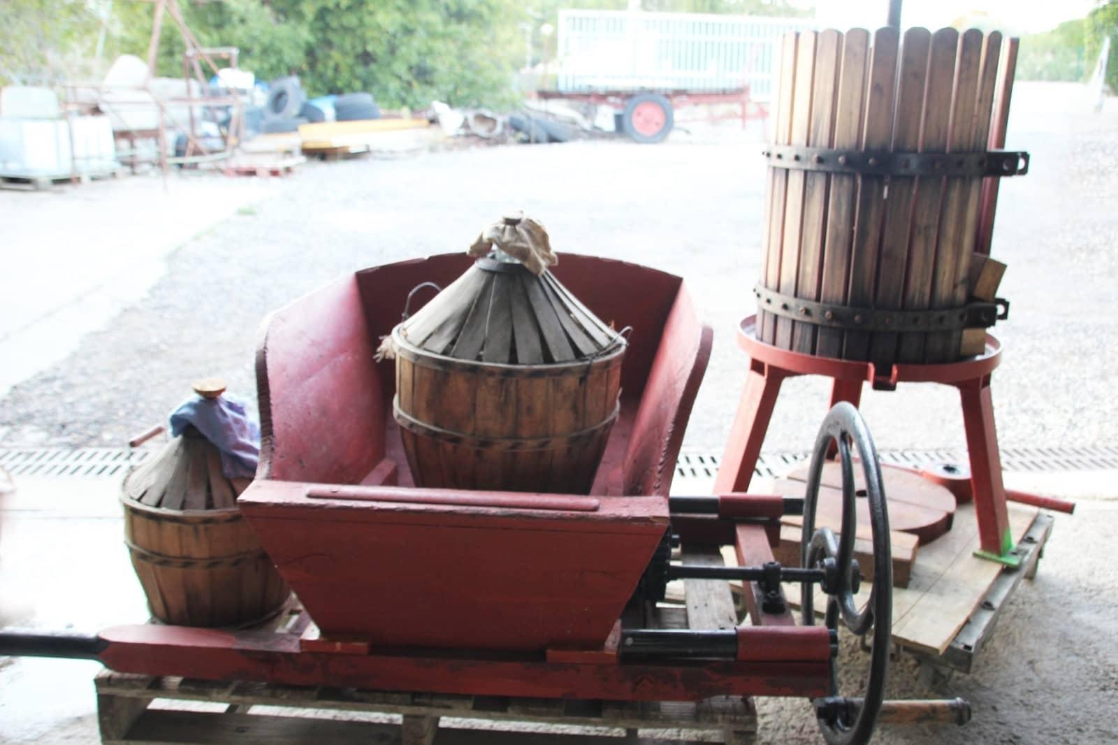 Pressoir et passoire pour le raisin avec des bonbonnes de vin
