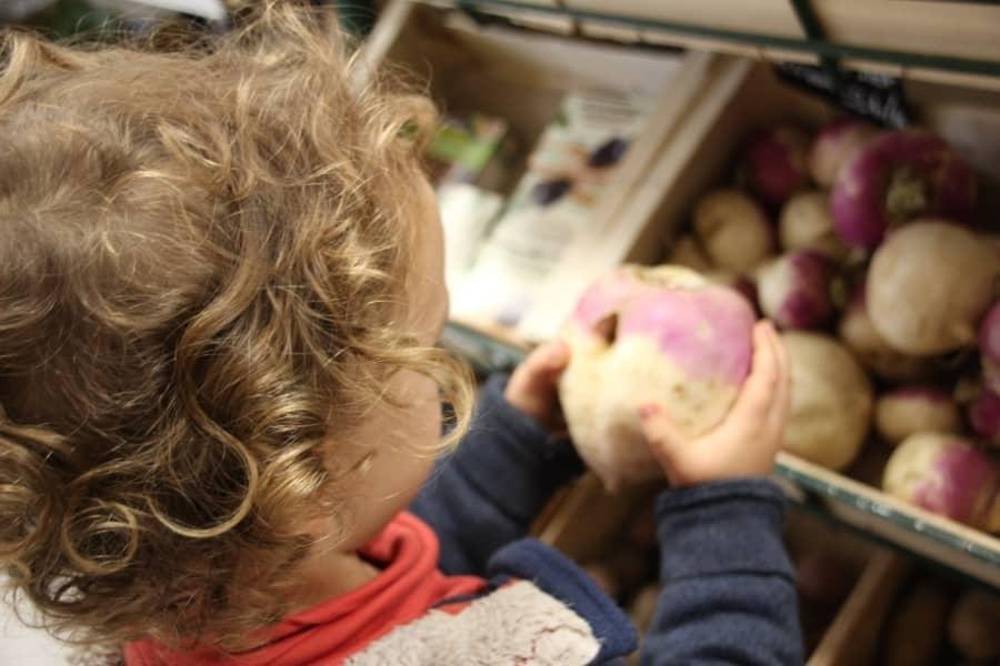 Enfant devant un étal de légumes